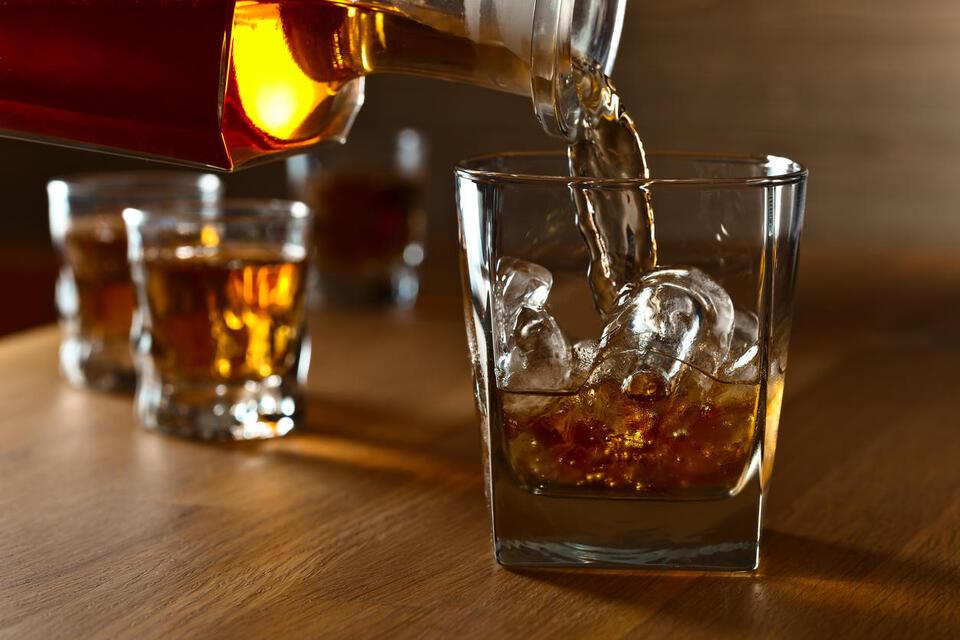 Pouring whiskey into glass with ice istock igorr1